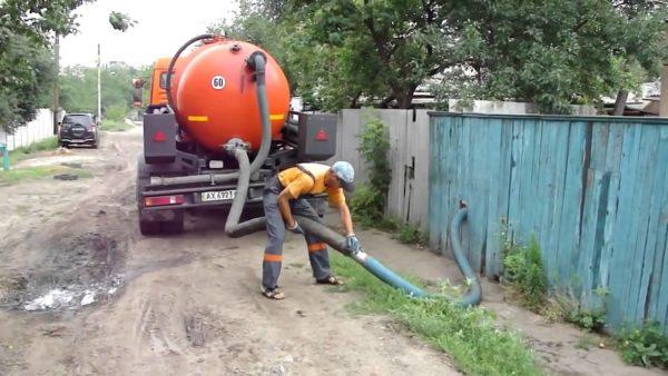 Ассенизаторская машина выполняет механическую очистку выгребной ямы