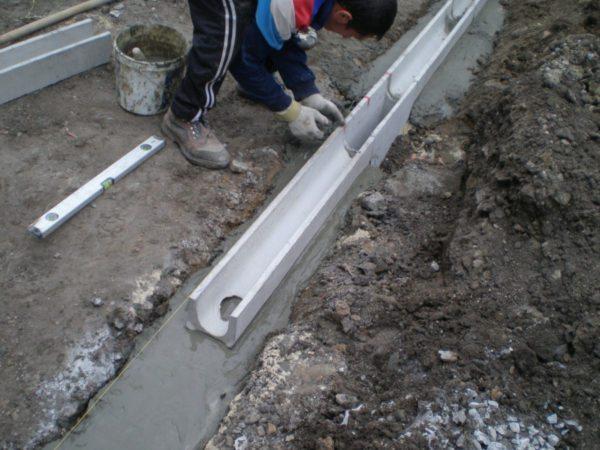 Бетонные лотки укладываются в траншею, заполненную цементным раствором.