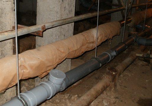 Канализационная лежневка в подвале многоквартирного дома.
