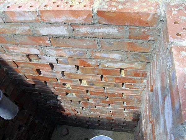 Кирпичная кладка выгребной ямы с зазорами.